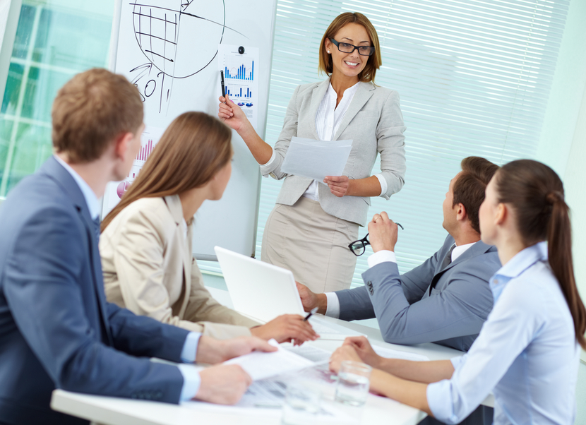Confident businesswoman explaining something to colleagues at meeting